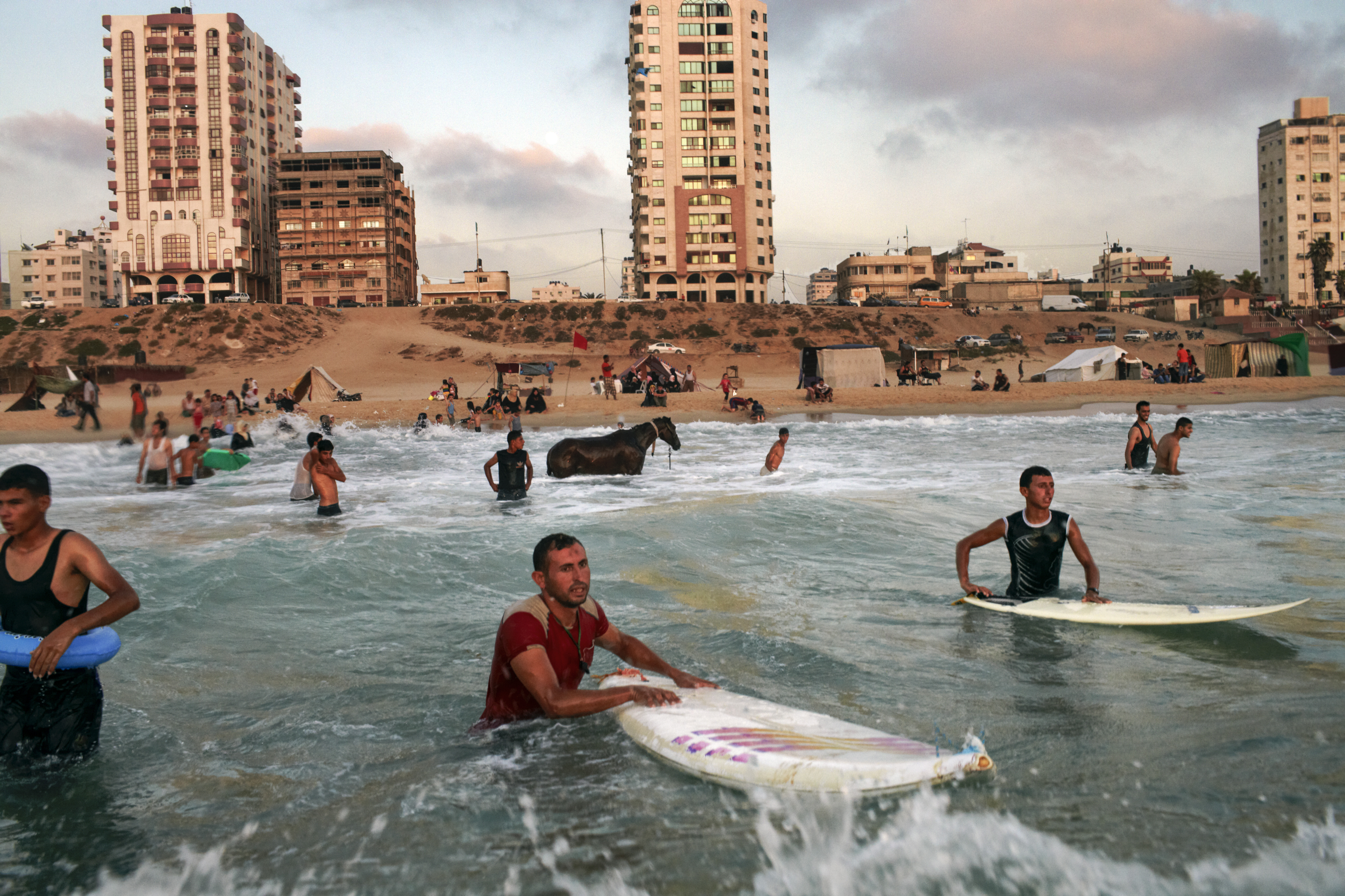 Still from the film Gaza shows Palestinian men surfing in the sea.